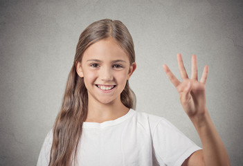 Headshot teenager girl showing 4 fingers on grey background