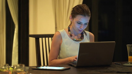 Beautiful businesswoman working on laptop at home during the nig