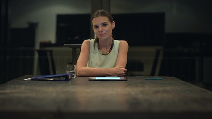 Portrait of serious, proud businesswoman sitting by table at nig
