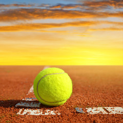 Tennis ball on a tennis clay court in the sunset