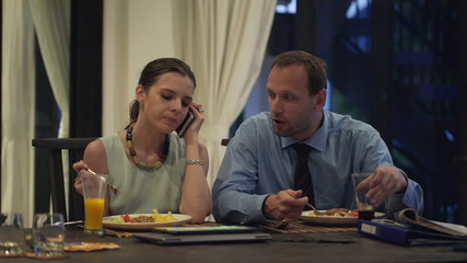 Business couple talking on cellphone and eating dinner at home i