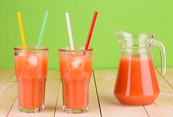 Two glasses full of tasty grapefruit juice.
