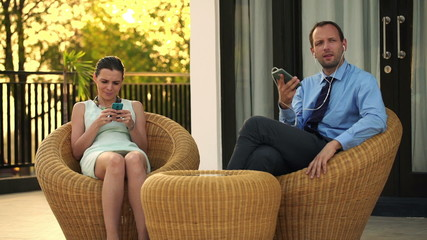 Business couple talking on cellphone by earphones and using smar