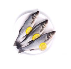Three raw seabass on plate.