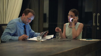 Business couple talking on cellphone, using tablet computer and