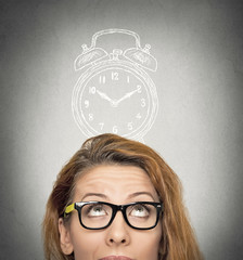 business woman with alarm clock above her head looking up