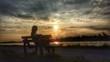 canvas print picture - Eine Frau sitzt auf einer Bank und genießt den Sonnenuntergang