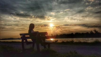 Eine Frau sitzt auf einer Bank und genießt den Sonnenuntergang
