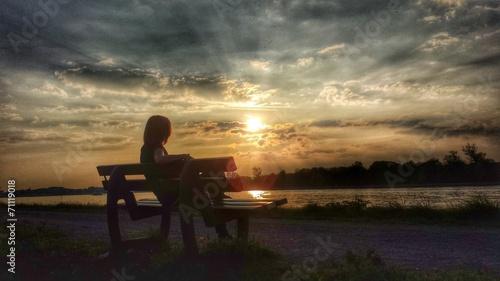 canvas print picture Eine Frau sitzt auf einer Bank und genießt den Sonnenuntergang