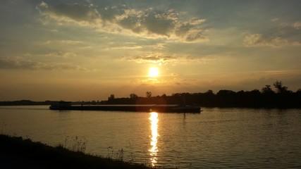 Ein Schiff während des Sonnenuntergangs auf dem Rhein