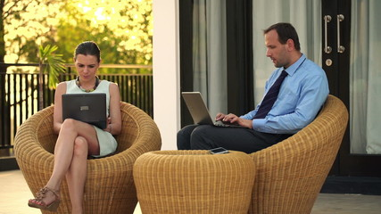 Business couple working on laptop on terrace