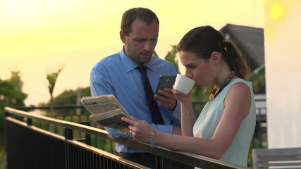 Business couple reading newspaper, drinking coffee and using sma