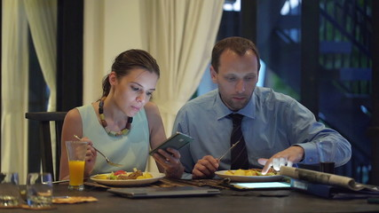 Business couple with smartphone and tablet computer eating dinne