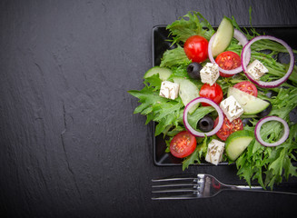 Fresh tasty salad on dark stone table