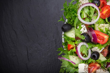 Fresh tasty salad on dark stone table