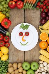 Gesicht aus Gemüse und Früchte auf Teller mit Tomaten und Äpf