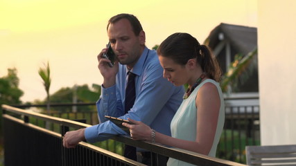Business couple talking on cellphone and using tablet computer o