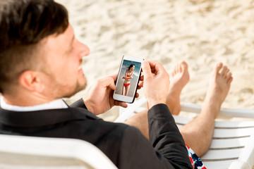 Businessman holding cellphone on the beach