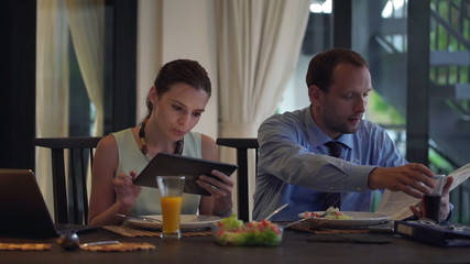 Business couple using tablet computer, reading newspaper and eat