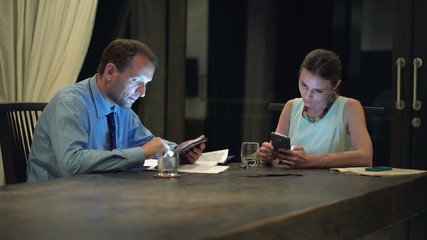 Business couple working on tablet computer and using smartphone