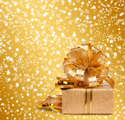 Gift box in gold wrapping paper on a beautiful  abstract backgro
