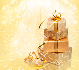 Gift box in gold wrapping paper on a beautiful abstract backgrou