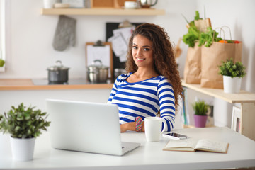 Smiling young woman with coffee cup and laptop in the kitchen at