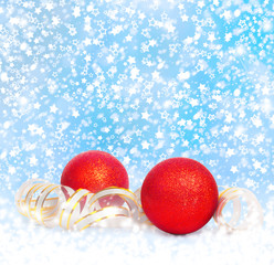 Red Christmas balls with golden streamer on a snowy blue backgro