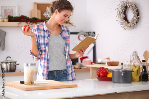 Young woman reading cookbook in the kitchen, looking for recipe - 71124095