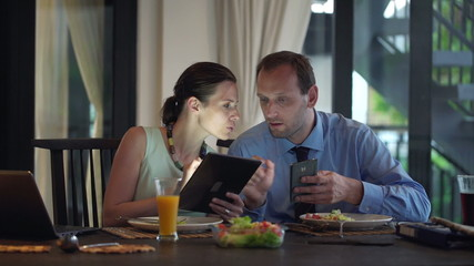 Business couple talking and comparing data on tablet and smatpho