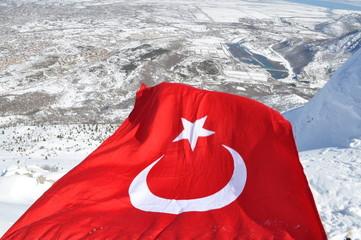 karlı dağlarda dalgalanan türk bayrağı