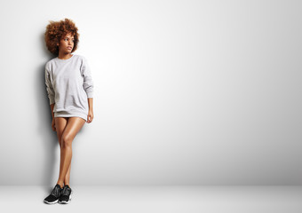 black woman with curly hair wearng sweatshirt like a dress