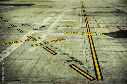 A picture of black and yellow airport markings on concrete - 71125045