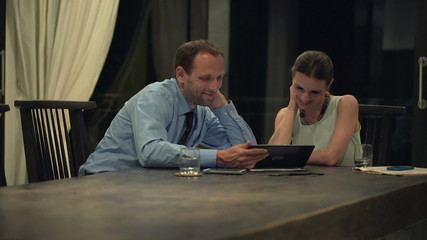 Business couple watching funny movie on tablet computer at home