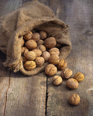walnuts in burlap bag on old wood table