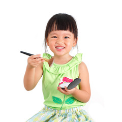asian little girl learning to make up