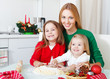 Two adorable girls with mother baking Christmas cookies in the k