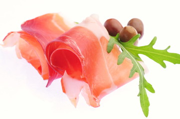Sliced prosciutto with rosemary and olives on white background