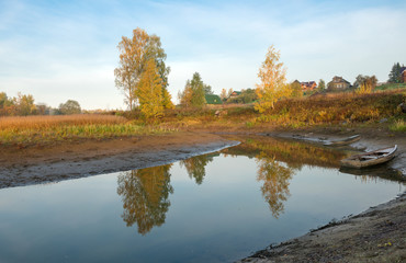 Small river flowing near the village autumn morning