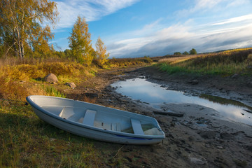 Boat on the dry river autumn morning