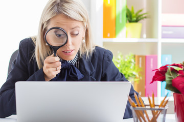 Woman looking at computer through a magnifying glass