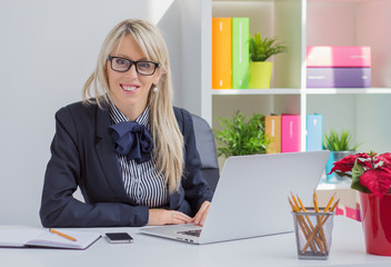 Portrait of young woman sitting at desk in office