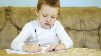 child writing alphabet at home