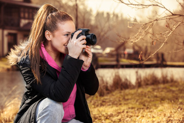 Woman holding camera and taking photo outside