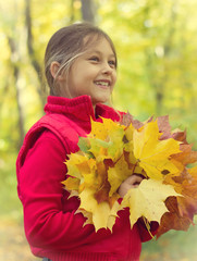 girl and a bouquet of autumn leaves