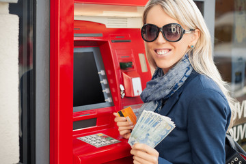 Young woman showing cash after withdrawal from ATM