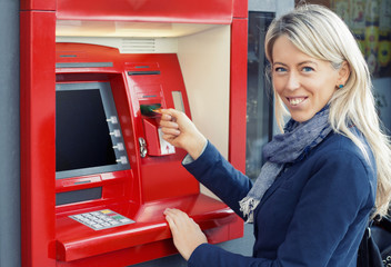 Happy woman using ATM to withdraw money