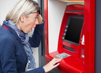Shocked woman looking at her bank account balance