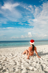 Woman in santa hat on the beach