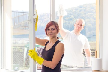 Young couple dusting windows at home